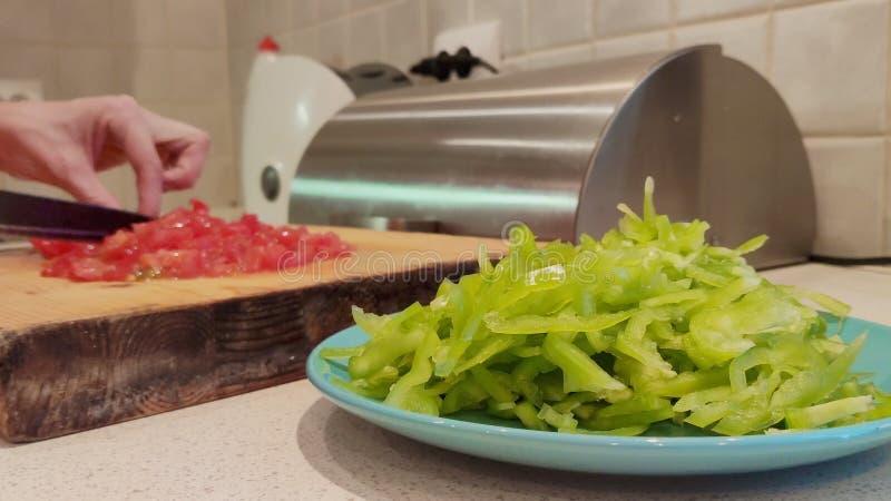 Un plan rapproché d'un plat de paprika vert finement haché dans la perspective des mains femelles coupant en tranches des tomates image stock