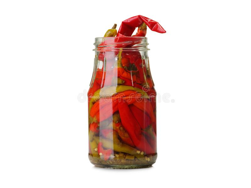 Un plan rapproché d'un pot en verre complètement de poivre de piment mariné rouge d'isolement sur un fond blanc Concept de nourri photo stock