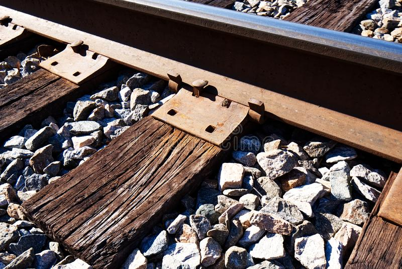 Un plan rapproché d'un rail de chemin de fer, des liens croisés superficiels par les agents et d'un ballast images libres de droits