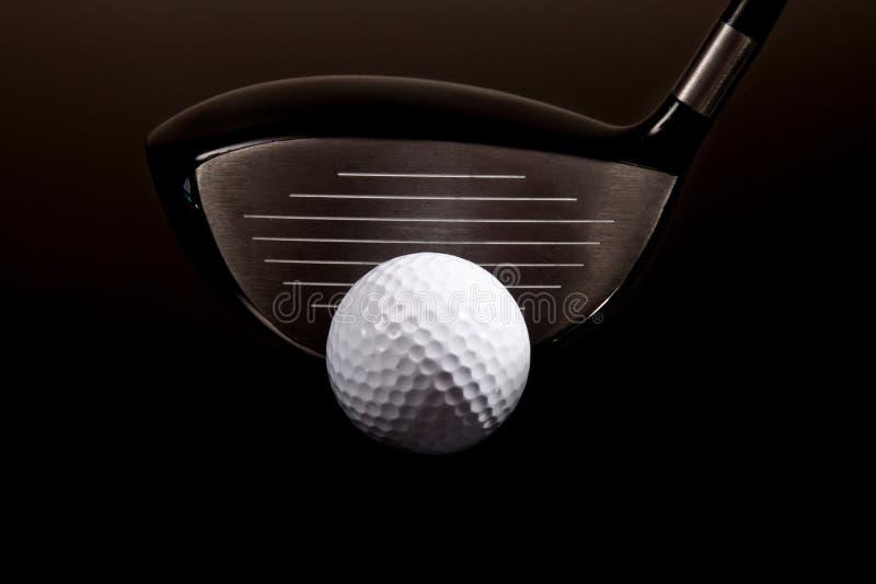 Un plan rapproché d'un gestionnaire de golf et d'une bille de golf sur le noir photo stock