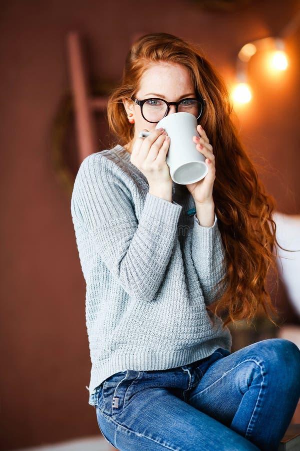 Un plan rapproché de belles mains femelles tenant une grandes tasse et boisson en verre La femme portant un hiver chaud a tricoté photographie stock
