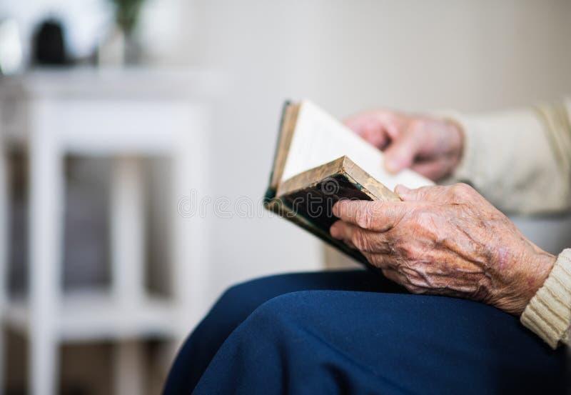 Un plan rapproché de bible supérieure de lecture de femme à la maison images libres de droits