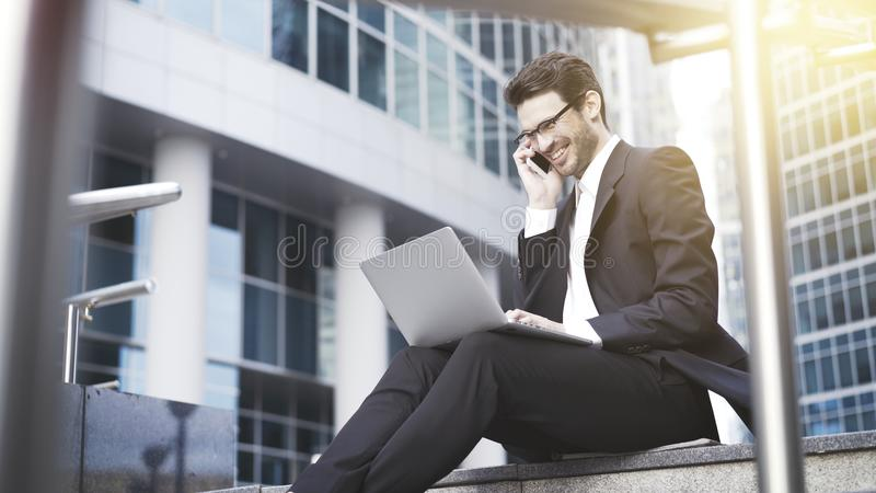 Un plan rapproché de jeune homme d'affaires riant heureux avec l'ordinateur portable ayant un appel images stock