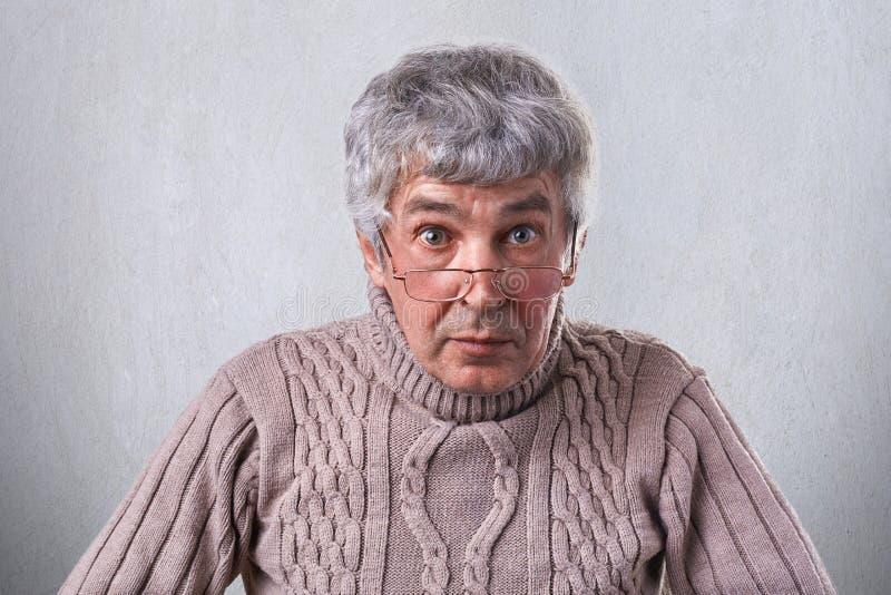 Un plan rapproché moyen horizontal d'un homme plus âgé avec les yeux gentils de cheveux gris ayant des rides sur les lunettes de  photo stock