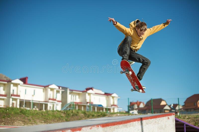Un planchiste d'adolescent fait un tour d'ollie dans un skatepark sur les périphéries de la ville image libre de droits