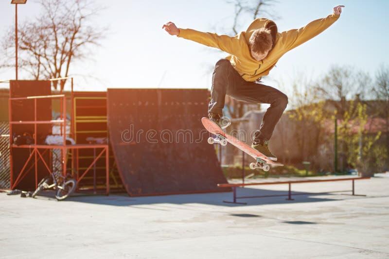 Un planchiste d'adolescent fait un tour d'ollie dans un skatepark sur les périphéries de la ville images stock