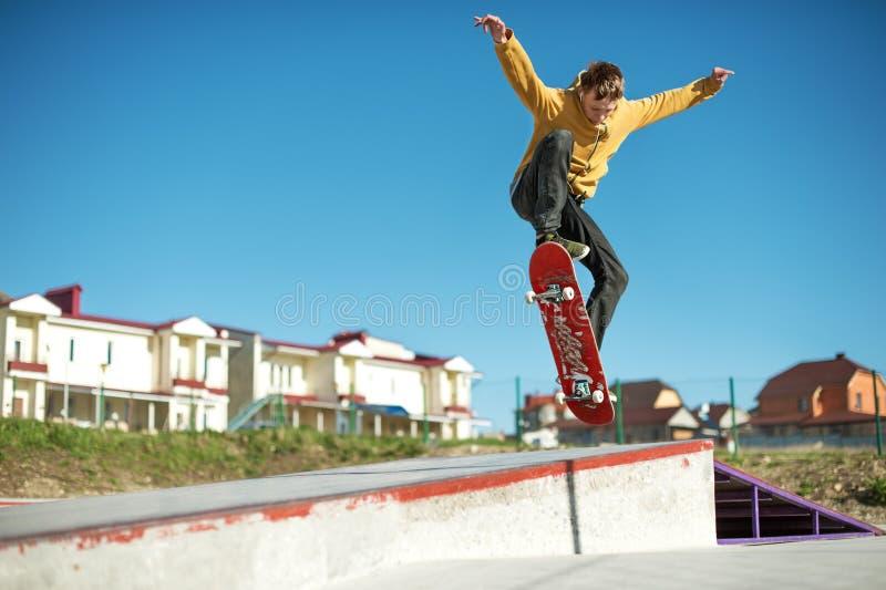Un planchiste d'adolescent fait un tour d'ollie dans un skatepark sur les périphéries de la ville photo stock