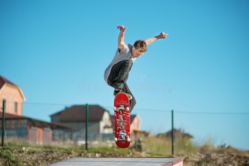 Un planchiste d'adolescent fait un tour d'ollie dans un skatepark sur les périphéries de la ville photos stock