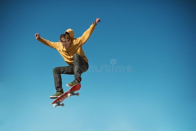 Un planchiste d'adolescent fait un tour d'ollie sur le fond du gradient de ciel bleu images stock