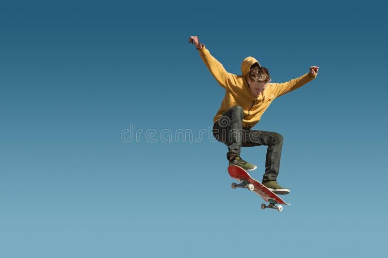 Un planchiste d'adolescent fait un tour d'ollie sur le fond du gradient de ciel bleu photos libres de droits