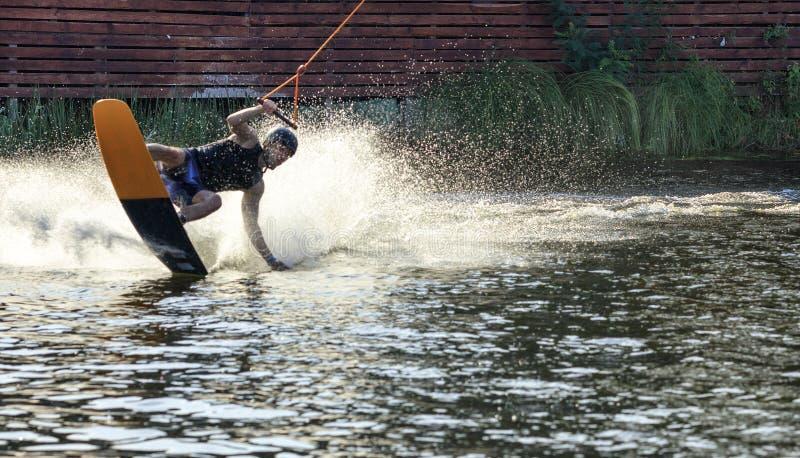 Un planeur de wakeboard se précipite dans l'eau à grande vitesse en soulevant une colonne d'eau à un virage rapide photo libre de droits