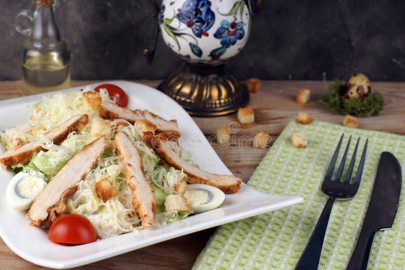 Un plat avec de la salade de César avec le poulet à côté d'une serviette et des couverts verts images libres de droits