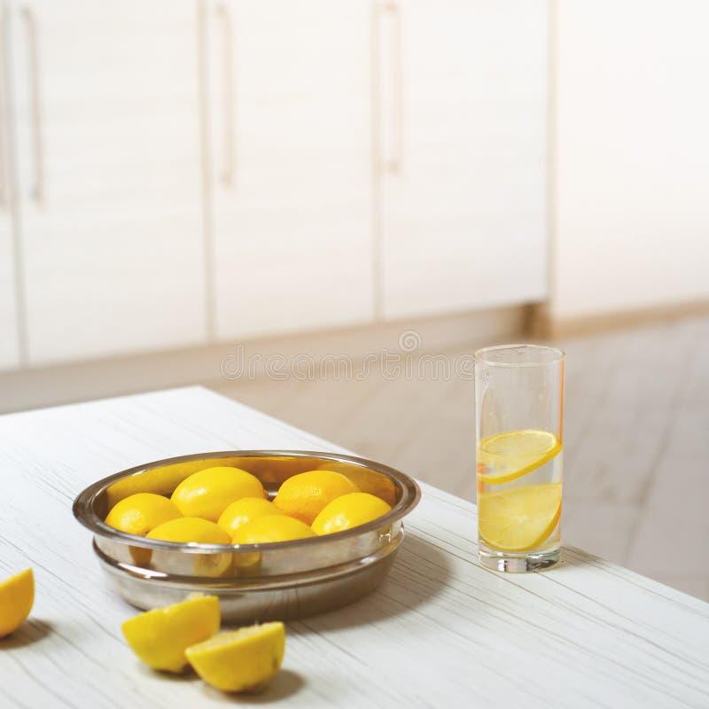 Un plat avec des citrons et un verre de limonade prête à l'emploi photographie stock
