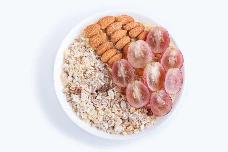 Un plat avec le muesli, amandes, raisins roses d'isolement sur un fond blanc image stock