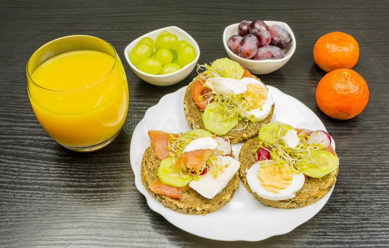 Un plat avec les sandwichs, le fruit et le jus sains à pain de seigle pour b photos libres de droits