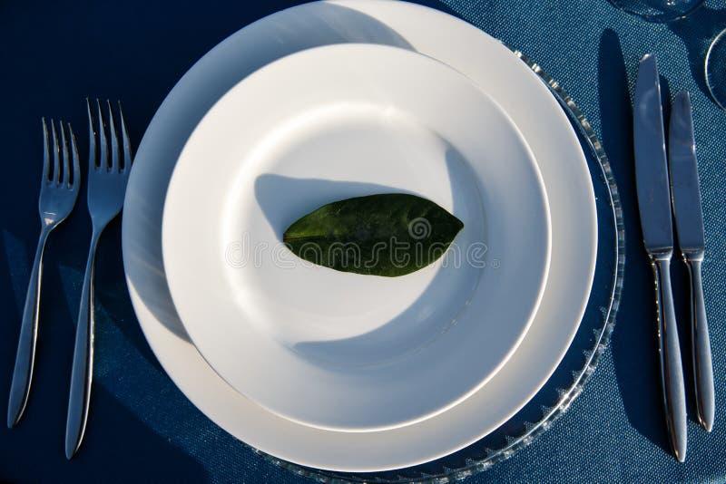Un plat avec une feuille décorative avec un nom russe là-dessus se tient sur une table Les couverts s'étendent les des deux côtés images libres de droits