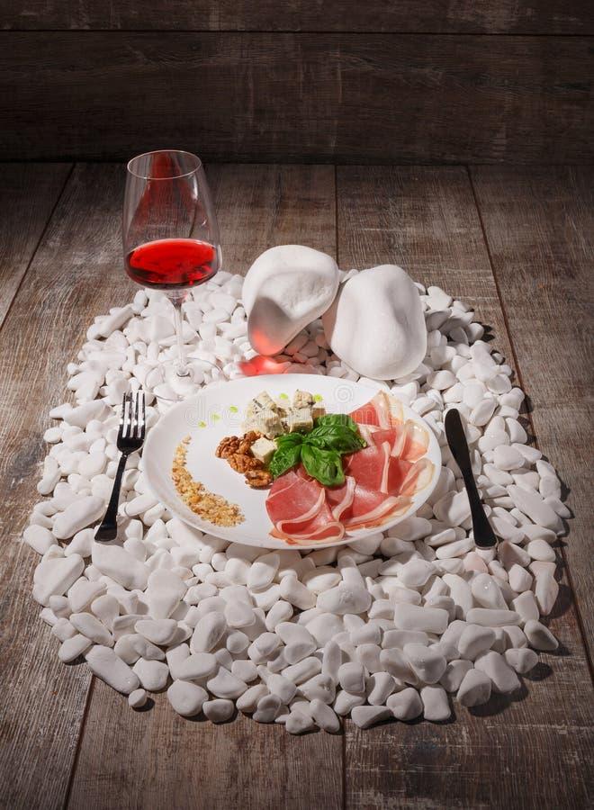 Un plat blanc complètement de prosciutto, de fromage, d'écrous et d'un verre à vin sur les pierres blanches et sur un fond en boi photographie stock libre de droits