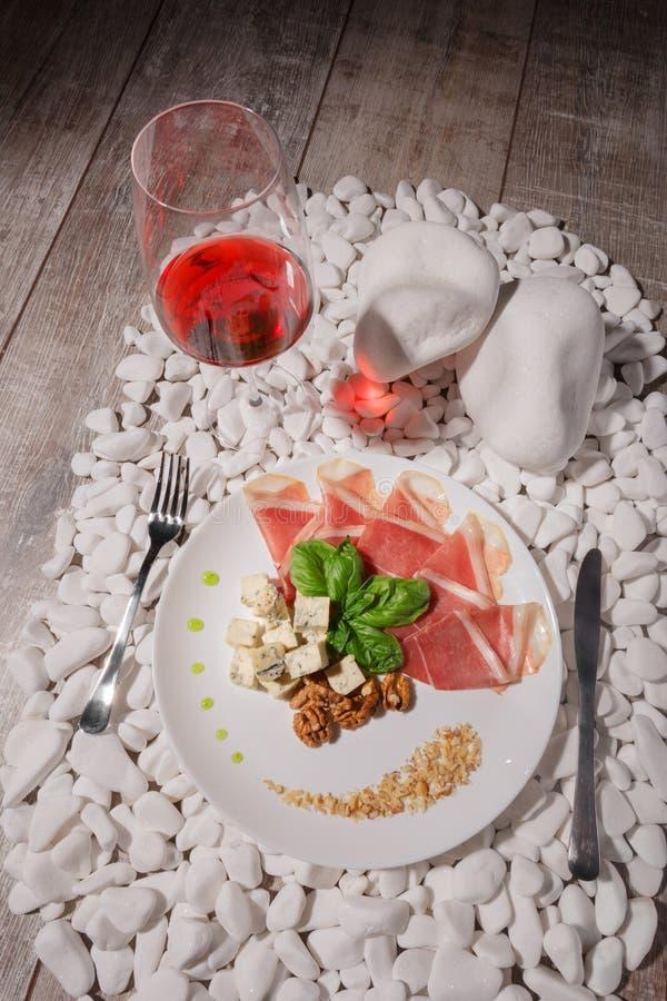Un plat blanc complètement de prosciutto, de fromage, d'écrous et d'un verre à vin sur les pierres blanches et sur un fond en boi photo stock