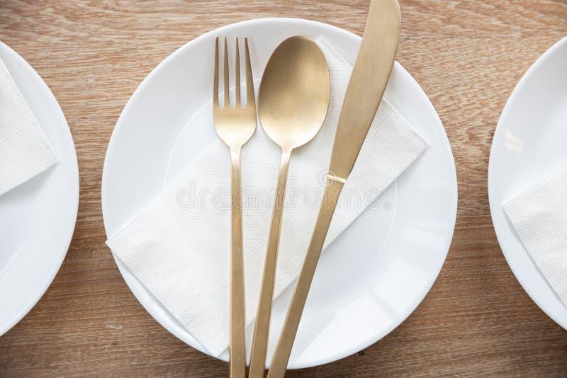 Un plat blanc de luxe, une fourchette d'or, une cuillère et un couteau avec la serviette de papier sur la table en bois photo libre de droits