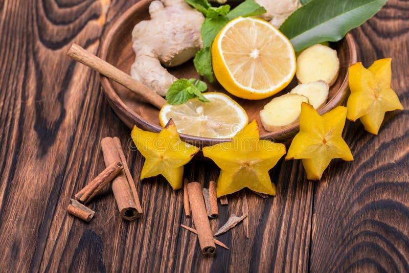 Un plat complètement d'un carambolier jaune, d'un citron aigre et d'une cannelle parfumée sur un fond en bois Ingrédients sains d photo stock