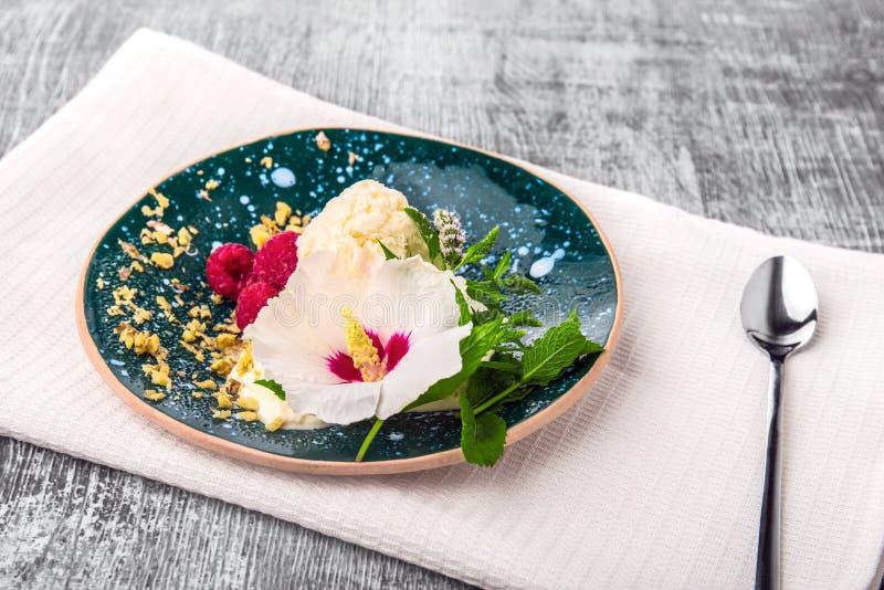 Un plat complètement d'une crème glacée avec les framboises roses douces sur un tissu blanc et sur un fond en bois Casse-croûte o images libres de droits