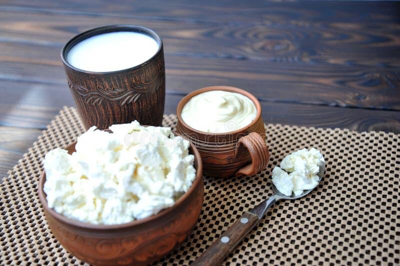 Un plat d'argile avec le fromage blanc, une tasse d'argile avec la crème sure, une tasse avec du lait et une cuillère avec le fro photo libre de droits