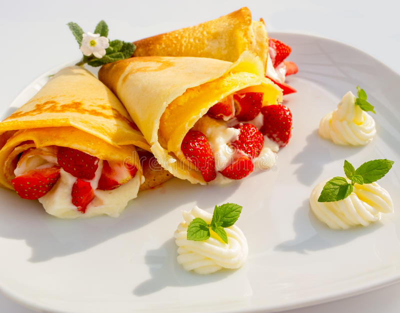 un plat de dessert avec des cr 234 pes des fruits de fraise la cr 232 me fouett 233 e et la menthe photo