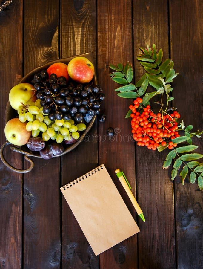 Un plat de fruit, un bloc-notes, stylo, crayons photographie stock