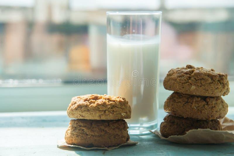 Un plat des biscuits de farine d'avoine de beurre d'arachide a servi avec un verre froid de lait Ces biscuits sont complètement v image libre de droits