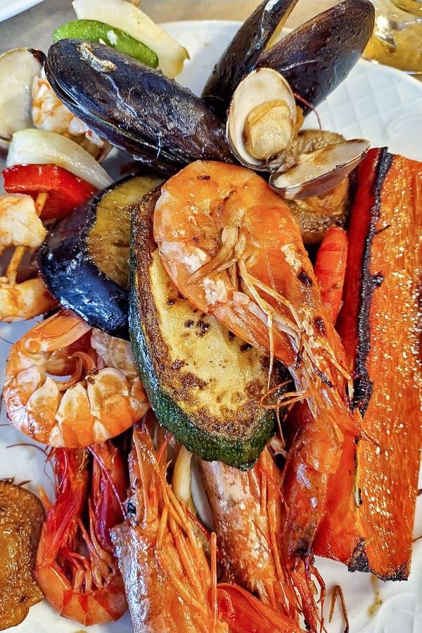 Un plato con los mariscos y las verduras asadas a la parrilla en primer Plato mezclado de los mariscos imagenes de archivo