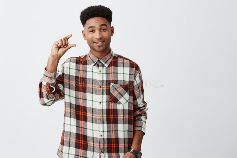 Un poco Retrato del individuo divertido de piel morena apuesto joven con corte de pelo afro en la sonrisa a cuadros de la camisa foto de archivo libre de regalías