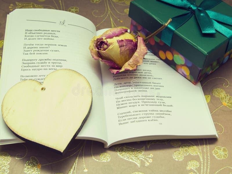 Un poema, un corazón de madera, rosas secadas y una caja con un regalo foto de archivo libre de regalías