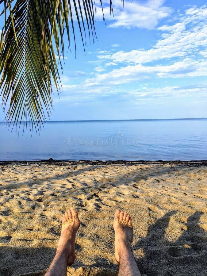 Un point de vue tiré avec les jambes et les pieds d'une apparence d'homme se trouvant sur une belle plage sablonneuse donnant sur images stock