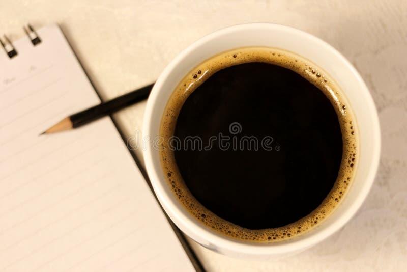 Un poli caliente negro de los soportes del café al lado de una libreta con una pluma foto de archivo libre de regalías