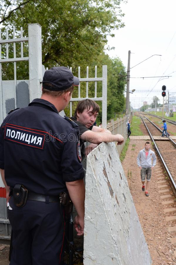 Un policier parle à un citoyen ivre sur une plate-forme ferroviaire photos stock