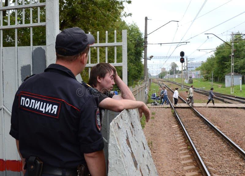 Un policier parle à un citoyen ivre sur une plate-forme ferroviaire photo libre de droits