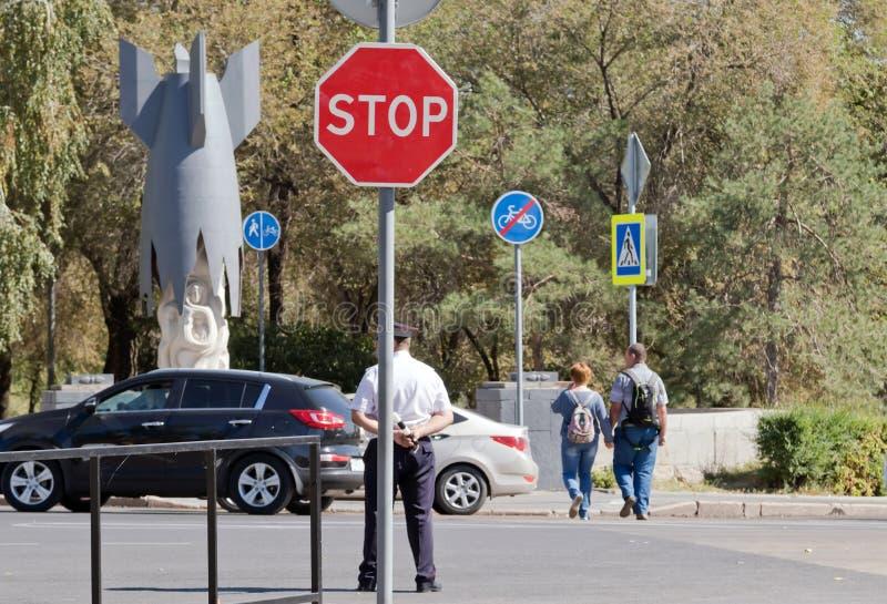 Un policier se trouve au tournant avec une tige dans des mains sur photographie stock