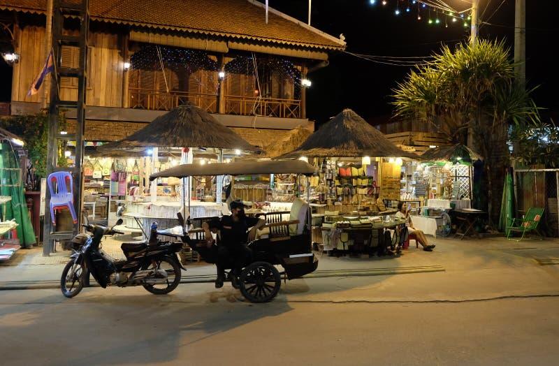 Un poliziotto si siede in un risciò del motore, bei chioschi con le merci per i turisti fotografie stock