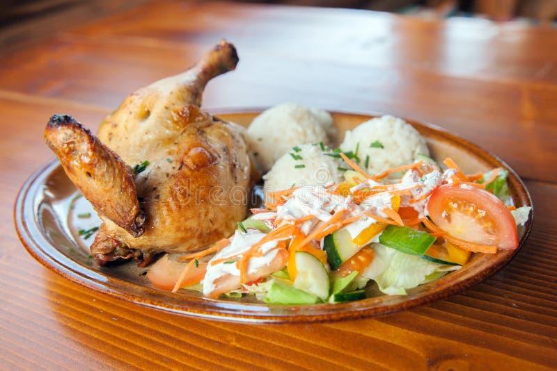 Un pollo asado con arroz hervido y ensalada fresca fotografía de archivo