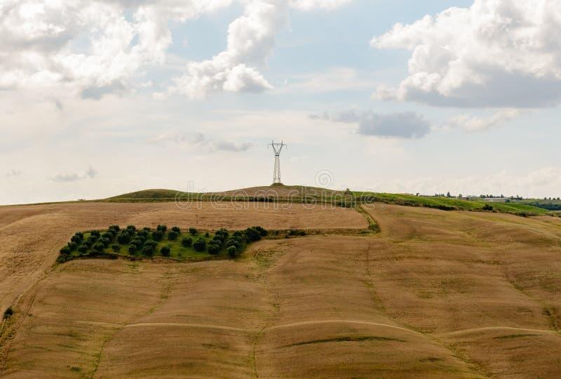 Un polo ligero contra un día nublado en la cima de una colina fotos de archivo