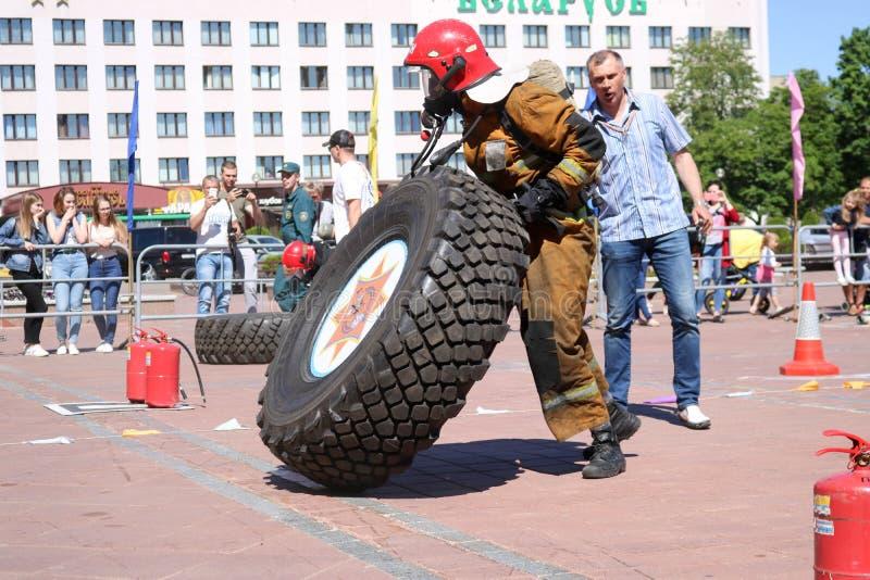 Un pompier dans un costume ignifuge court et tourne un grand en caoutchouc roulent dedans une concurrence de lutte contre l'incen images stock