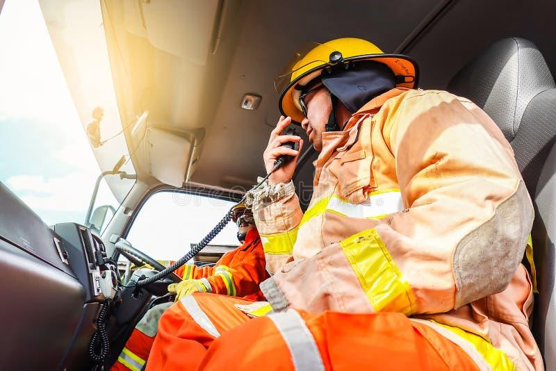 Un pompiere nel vestiario di protezione ed in un casco si siede in un veicolo di soccorso e nei colloqui del carico sulla radio immagini stock libere da diritti