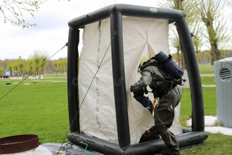 Un pompiere professionista in un vestito a prova di fuoco speciale nero prepara montare una tenda bianca dell'ossigeno alla gente immagini stock