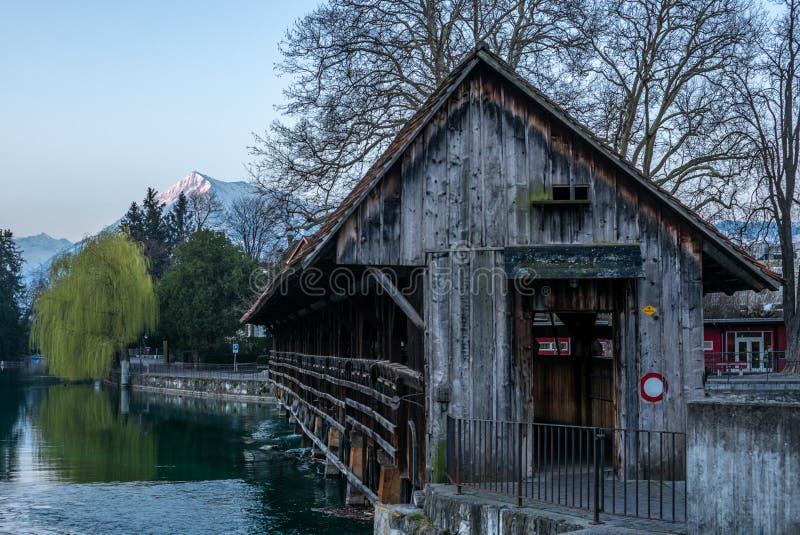 Un pont en bois traversant la rivière Aare dans Thun avec les montagnes de Jungfrau et d'Eiger à l'arrière-plan tôt le matin  photo stock