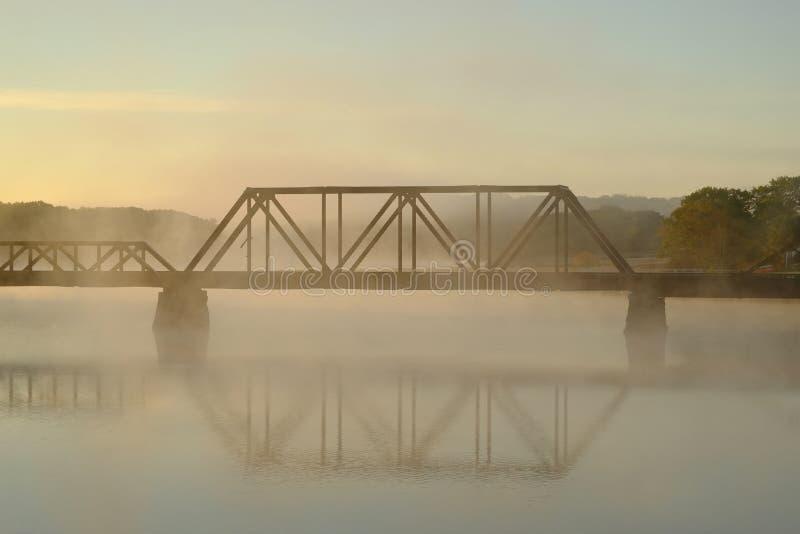 Un ponte della ferrovia sopra un fiume nebbioso e nebbioso Mo in anticipo immagine stock libera da diritti