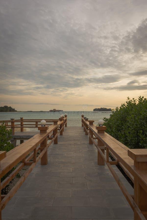 Un ponte di pietra che conduce ad un posto per godere del tramonto sull'isola reale, Indonesia Circondato dalle foreste della man immagine stock libera da diritti