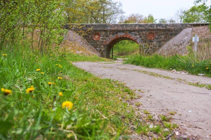 Un ponte ferroviario incurvato sopra la strada, vecchio viadotto di pietra fotografie stock libere da diritti