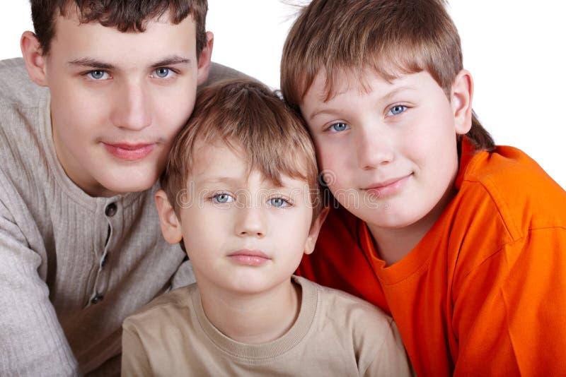 Un poprtrait del primo piano di tre ragazzi fotografia stock