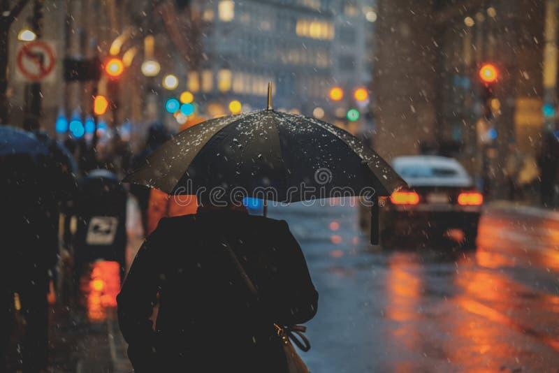 Un port de personne noir avec le parapluie noir pendant un jour neigeux photographie stock