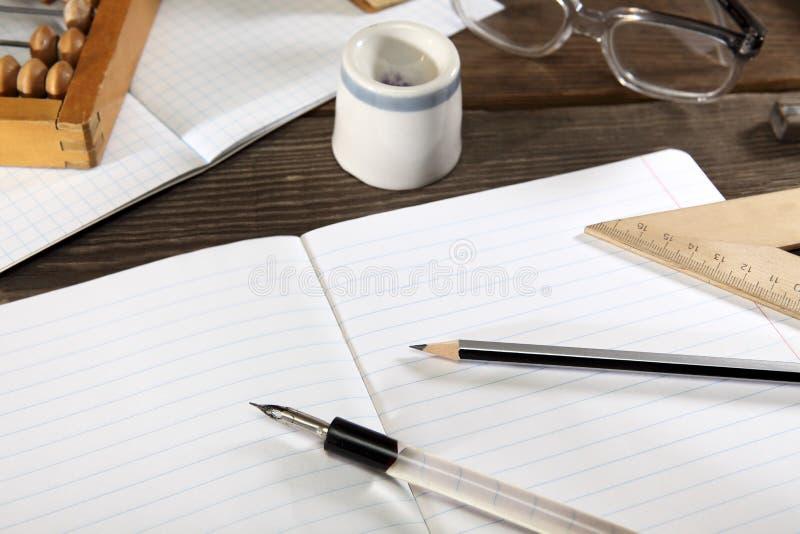 Un portapluma con una pluma, un lápiz simple, la regla, el ábaco y los vidrios mienten en un cuaderno abierto Foto estilizada ret fotografía de archivo libre de regalías